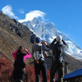 Tre vandrare fotograferar bergen i närheten av Everest Basecamp