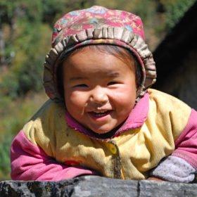 En Sherpaflicka ler mot vandrarna på väg till Everest Basecamp