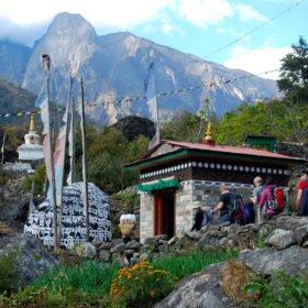 Vandrare går förbi buddhistiska flaggor och stenar på väg till Everest Basecamp