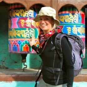 En kvinnlig vandrare snurrar på färgglada bönesnurror - på väg mot Everest Basecamp
