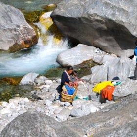 En Sherpakvinna har tvättat sina kläder och torkat dem på klipporna vid en å vid stigen mot Everest Basecamp
