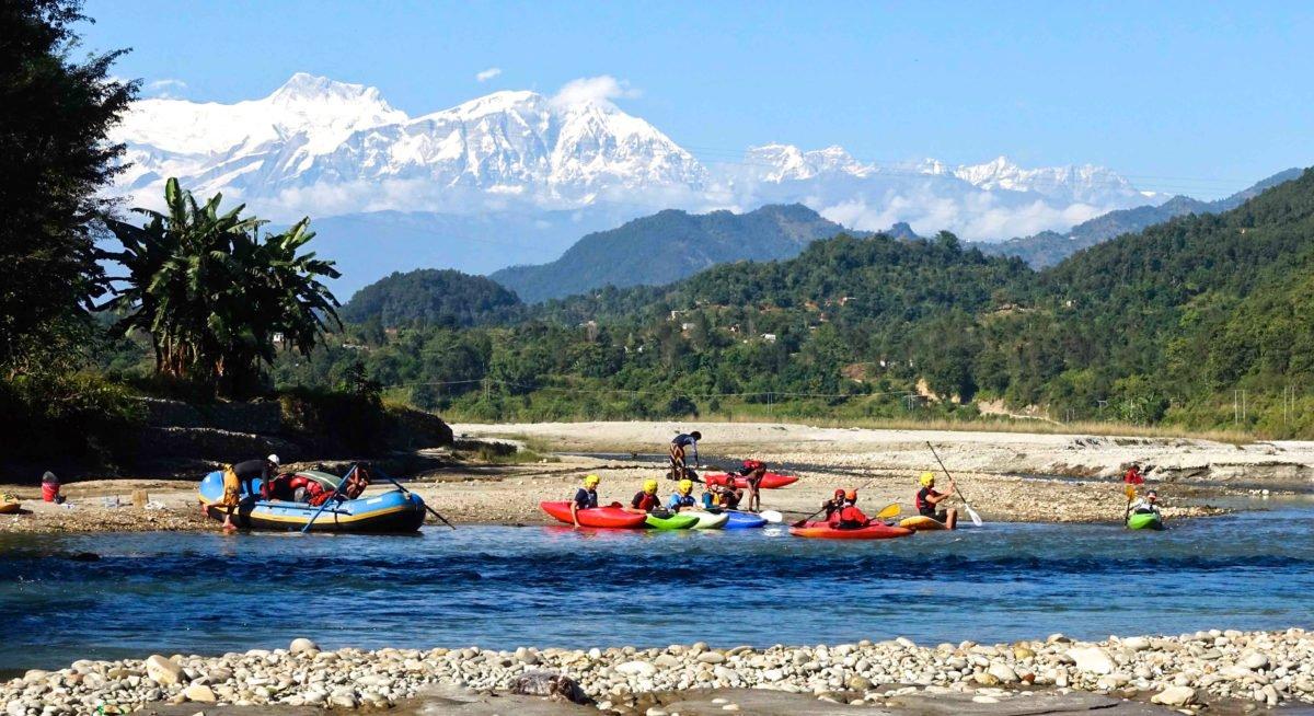 Kajaker vid en flod och berg i bakgrunden