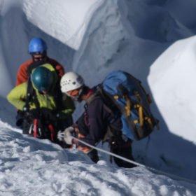 En guide hjälper till med repen högt uppe på Island Peak