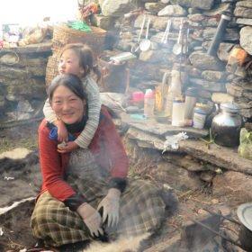 kvinna med barn i ett enkelt kök på Bhutan vandring