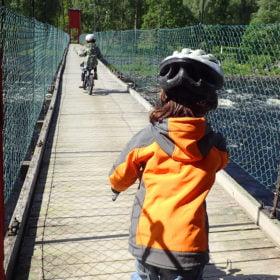 barn cyklar över bro