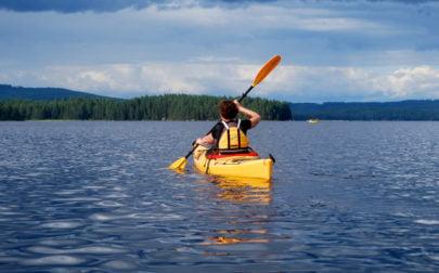 kvinna paddlar kajak på en sjö