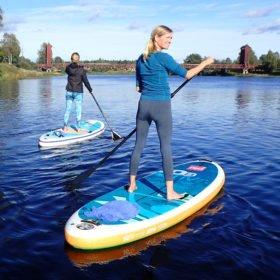 två tjejer på varsin bräda på SUP-paddling