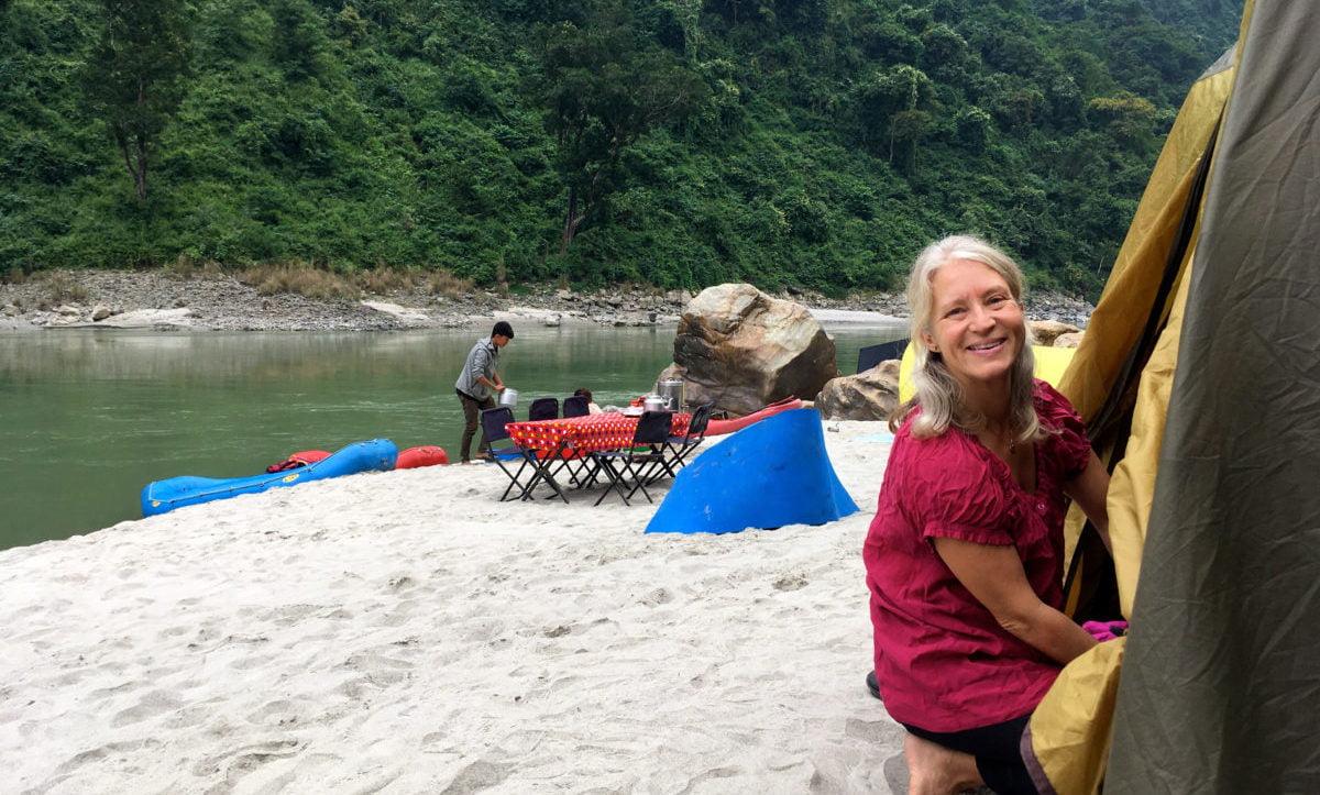 Anna sitter vid sitt tält på sandstrand på äventyrsresa
